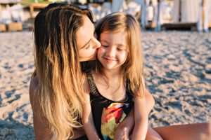 close-up-portrait-of-young-attractive-mother-with-little-beautiful-daughter-dressed-in-black-swim-suits-on-the-summer-beach v2